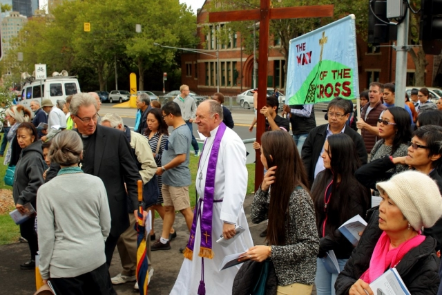 Image of Ric Holland leading the Way of the Cross Melbourne 2016 in front of the Cross and the Banner