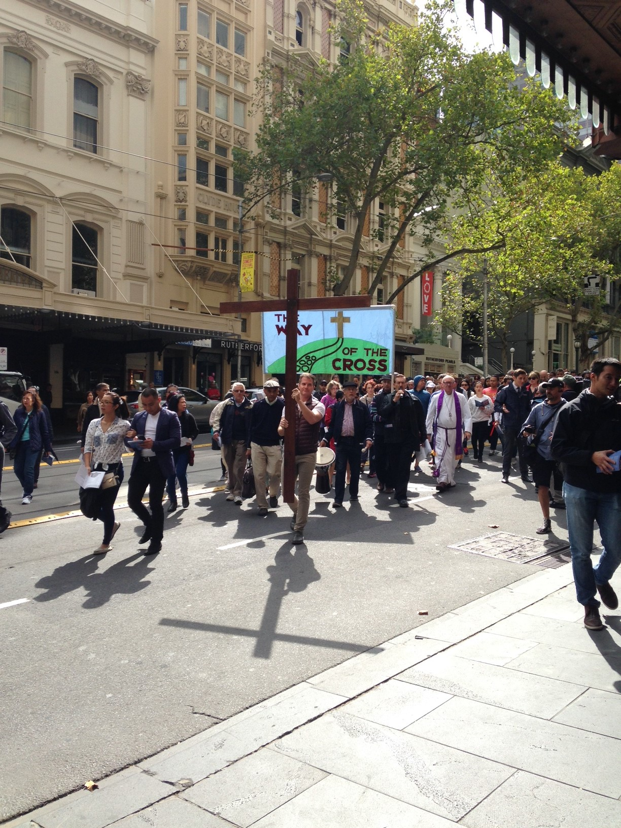 The Way of the Cross moves down Collins Street, the shadow of the cross preceding the cross itself and the banner