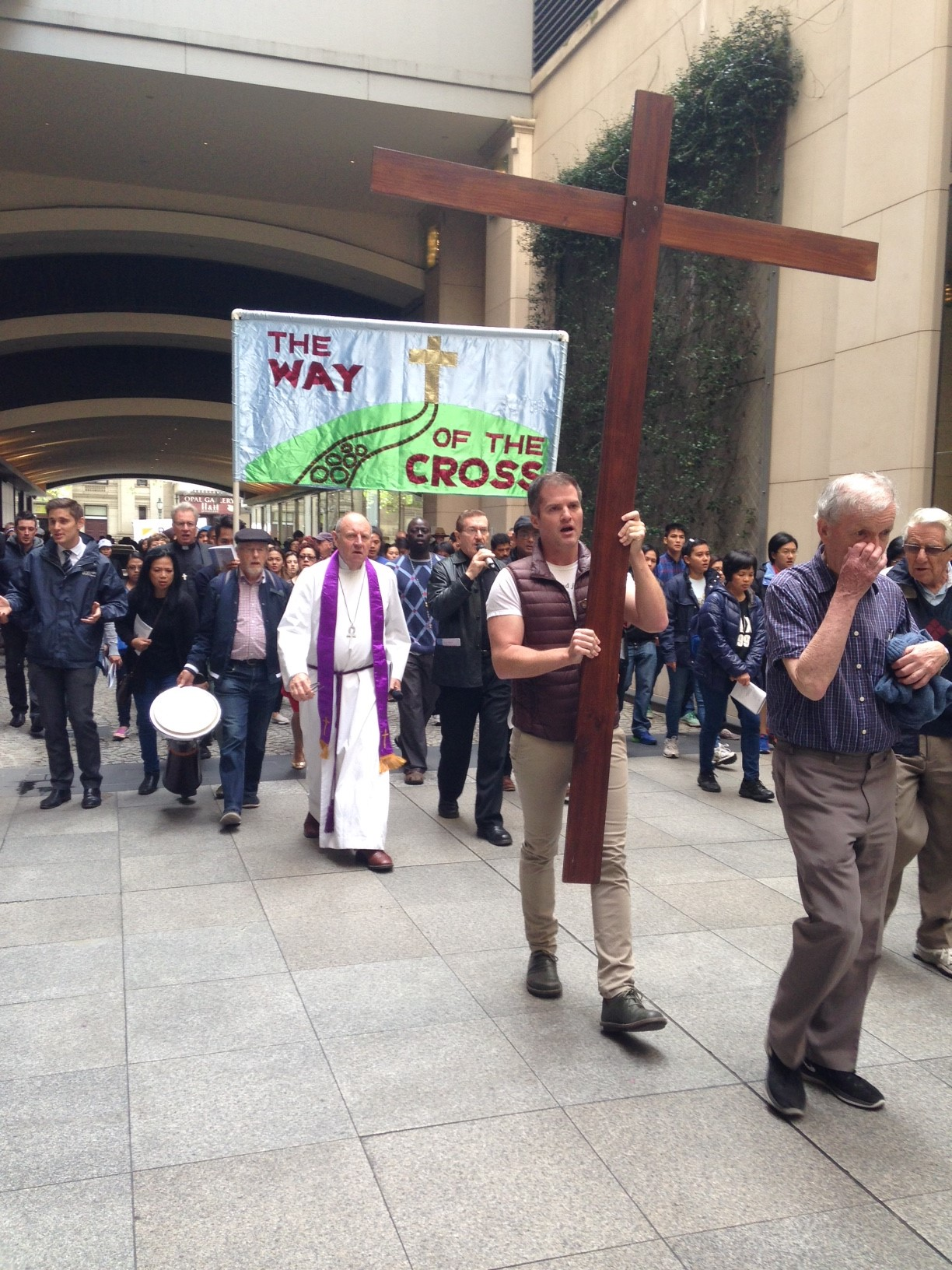 The Way of the Cross 2016, the cross and banner lead the procession through the Westin Hotel forecourt to St Paul's Cathedral - 550KB