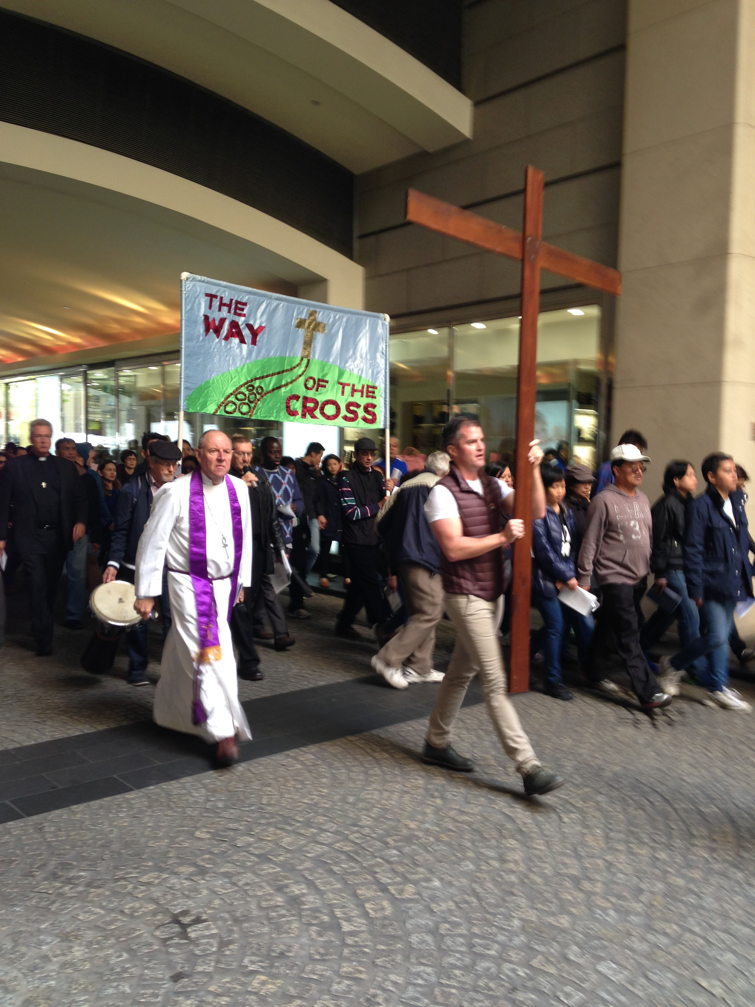 The Way of the Cross 2016 banner and cross pass beneath the arch of the Westin Hotel
