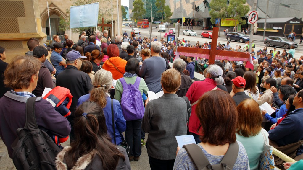 A large crowd in Flinders Street listens to the final station of the Way of the Cross at Saint Paul's Anglican Cathedral Melbourne Good Friday 2016